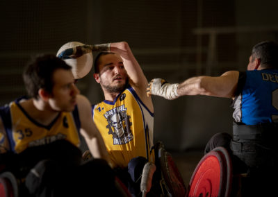 wheelchair rugby athlete protects opponents' ball