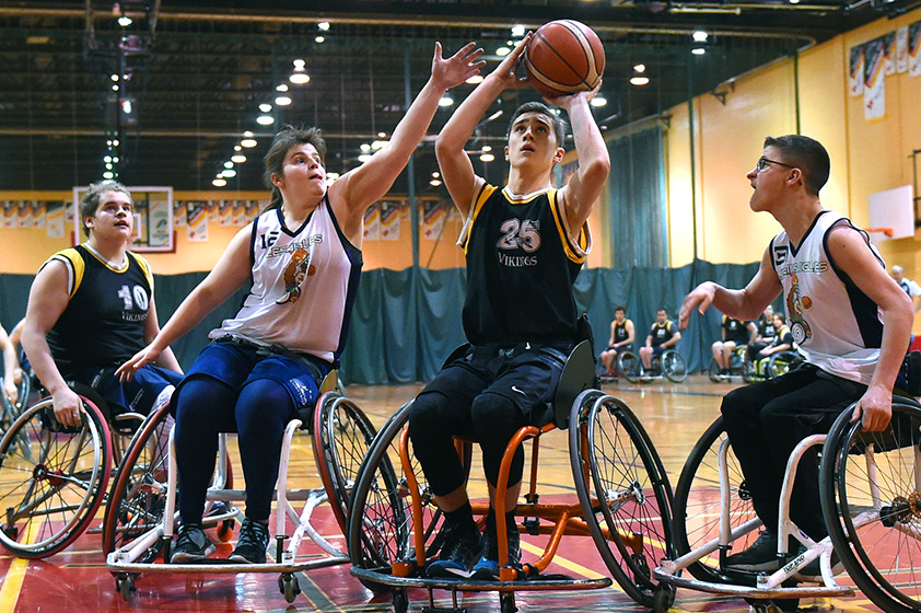An athlete in a wheelchair preparing to throw the ball in the hoop during a basketball game.