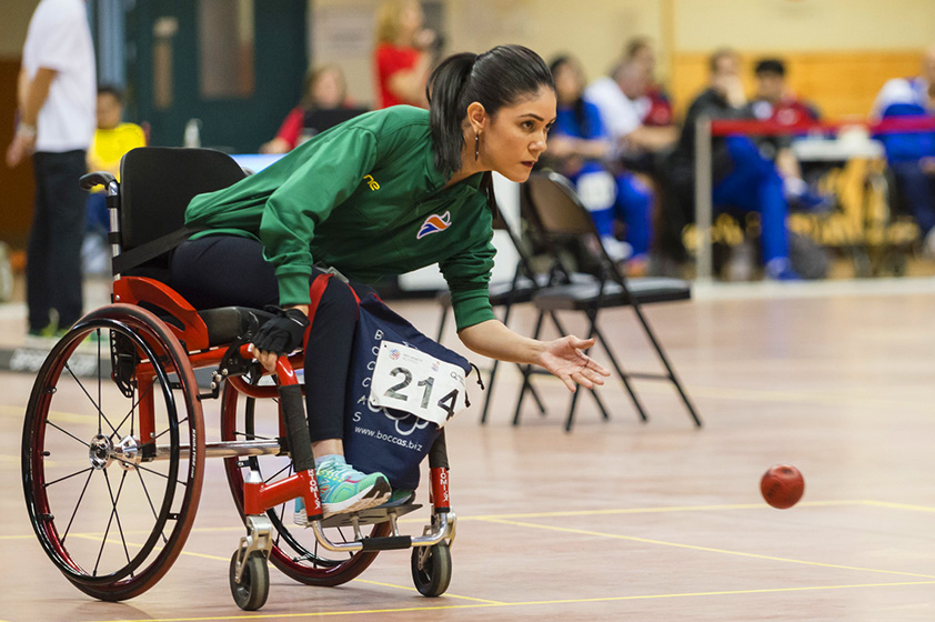 An elite athlete in a wheelchair throwing a boccia ball.