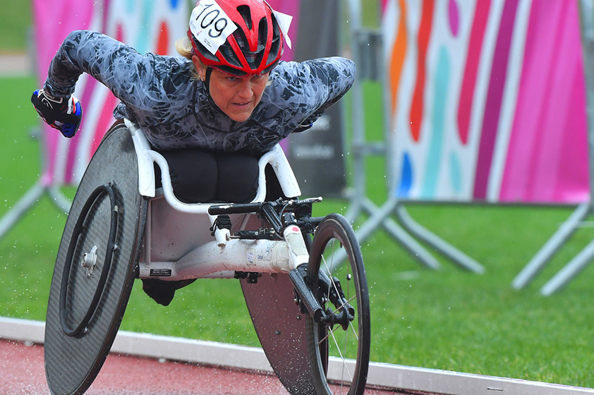 An athlete in a wheelchair racing on athletics tracks.