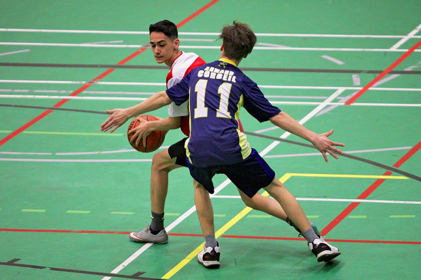 Two young athletes in motion during a basketball game.