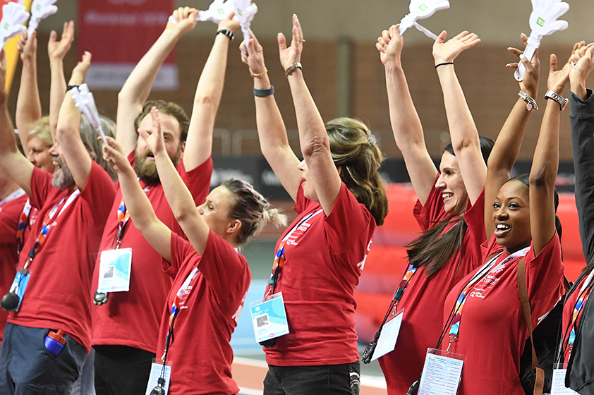 Smiling volunteers raising their hands skywards while standing by the guard of honour.