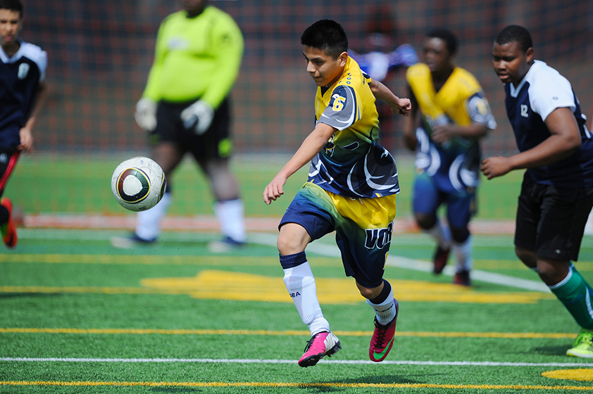 An athlete running after the ball during a soccer game.