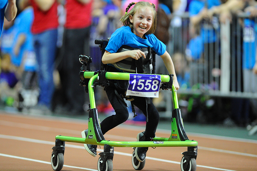 Young athlete moving forward with her walker on athletics tracks.